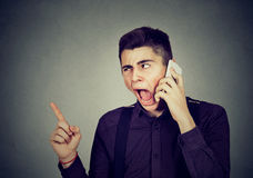 Angry young man screaming on mobile phone. Angry man screaming on mobile phone Royalty Free Stock Photos