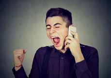 Angry young man screaming on mobile phone. Angry man screaming on mobile phone Stock Photography