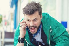 Angry young man screaming on mobile phone outdoors. Closeup of an angry young man screaming on mobile phone sitting outside with city street background. Negative Royalty Free Stock Photos