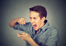 Angry young man screaming on mobile phone. Portrait angry young man screaming on mobile phone isolated on gray wall background. Negative human emotions feelings Royalty Free Stock Photos