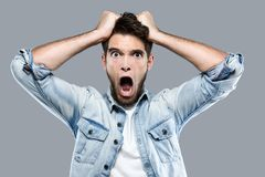 Angry young man screaming over gray background. Royalty Free Stock Photos