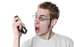 Angry young man screams into phone. Young 18 year old adult teenager yells into his wireless phone isolated on white background Royalty Free Stock Photo