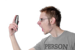 Angry young man screams into phone. Young 18 year old adult teenager yells into his wireless phone isolated on white background Royalty Free Stock Photography