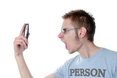 Angry young man screams into phone Royalty Free Stock Photography