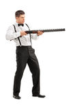 Angry young man shooting at something. With a shotgun isolated on white background Royalty Free Stock Photography