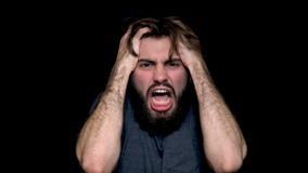 Angry young man shouting, expressing negative emotions, tearing his hair out, isolated on black background. Close up of stock image