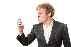 Angry young man shouting on the phone. Isolated on white Royalty Free Stock Photography