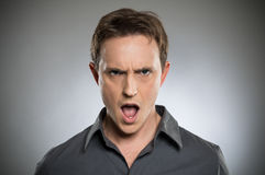 Angry Young Man Shouting. Portrait Of Angry Young Man Shouting Over Grey Background Stock Images
