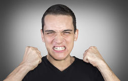 Angry young man showing his fists over neutral background Royalty Free Stock Photo