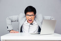 Angry young man sitting at the table. With laptop and looking at camera over gray background Royalty Free Stock Photo
