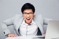 Angry young man sitting at the table. With laptop and screaming on camera over gray background Royalty Free Stock Image