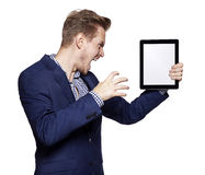 Angry young man and tablet PC Royalty Free Stock Photos
