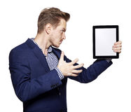 Angry young man and tablet PC Royalty Free Stock Photography