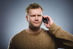Angry young man talking on cell phone isolated on gray background Royalty Free Stock Image