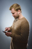 Angry young man talking on cell phone isolated on gray background Royalty Free Stock Photography
