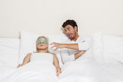 Angry young man teasing sleeping woman in bed Royalty Free Stock Photography