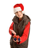 Angry young man with unwanted gift. Portrait of young angry christmas man showing unwanted gift isolated on white background. What is it Stock Photos