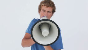 Angry young man using a megaphone Royalty Free Stock Images