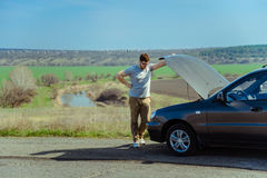 Angry young man waiting a help while sitting near the broken car Stock Photography