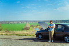 Angry young man waiting a help while sitting near the broken car Royalty Free Stock Photography