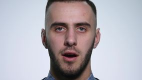 Angry young man On white Background. close up. slow motion.  stock video footage