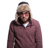 Angry young man in winter clothes and fur hat. Looking at the camera on white background Stock Image