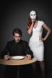 Angry young man beside woman. Angry young man with empty plate holding knife and fork looking aggressively with young woman in a white mask standing beside him Stock Photography