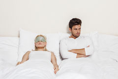 Angry young man with woman sleeping in bed Stock Photos
