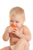 Angry young sitting baby bitting orange ball Stock Image
