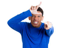 Angry young unhappy man displaying loser sign pointing at you in disgust Stock Photo