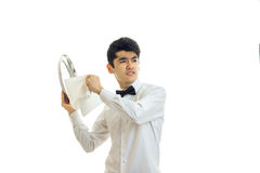 Angry young waiter cleaning silver tray and looking away. Isolated on white background royalty free stock images