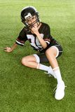 angry young woman in american football uniform sitting on grass and looking