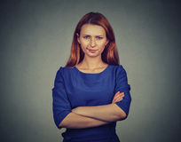 Angry young woman, being skeptical, displeased. Closeup portrait of angry young woman, being skeptical, displeased isolated on gray wall background. Negative Stock Photo
