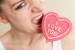 Angry Young Woman Biting Heart Shaped Royalty Free Stock Images