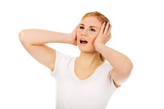 Angry young woman covering ears with hands.  Royalty Free Stock Image