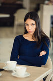 Angry young woman with crossed arms at cafe Royalty Free Stock Images