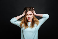 Angry young woman expressing disgust in the black colored studio Royalty Free Stock Photography