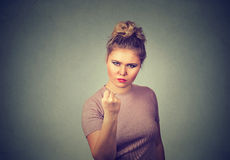 Angry young woman with fist up Stock Photo