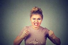 Angry young woman with fists up screaming Stock Images