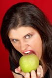 Angry young woman with green apple Royalty Free Stock Images