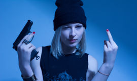 Angry young woman with a gun making obscene finger gesture Royalty Free Stock Image