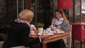 An adult daughter quarrels with her elderly mother in street cafe in the spring.