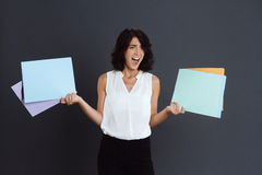 Angry young woman holding documents in hands. Over grey background stock photography