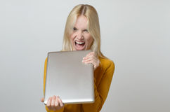 Angry Young Woman Holding her Laptop Computer Stock Images