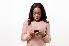 Angry young woman holding her mobile. Phone in her hand as she lookes shocked on it stock images