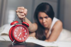 Angry young woman kill off alarm clock by fist on the bed in the morning royalty free stock photography
