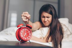 Angry young woman kill off alarm clock by fist on the bed in the morning royalty free stock photo