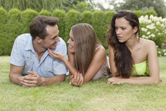 Angry young woman looking at loving couple at park Stock Photo