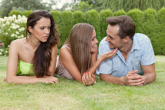 Angry young woman looking at loving couple at park Royalty Free Stock Photography