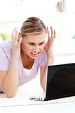 Angry young woman lying on the floor using laptop Stock Image